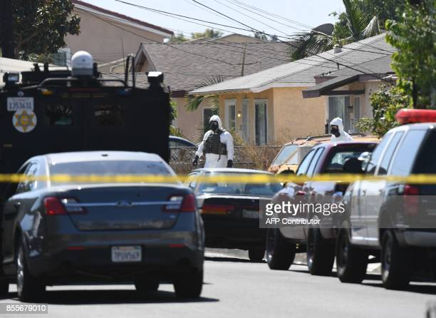 Members of the Los Angeles County Sheriff's Department bomb and hazmat squad search a house where a large amount of military ordnance including...