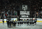 Members of the Los Angeles Kings look on as their championship banner is raised before the NHL season opener against the San Jose Sharks at Staples...