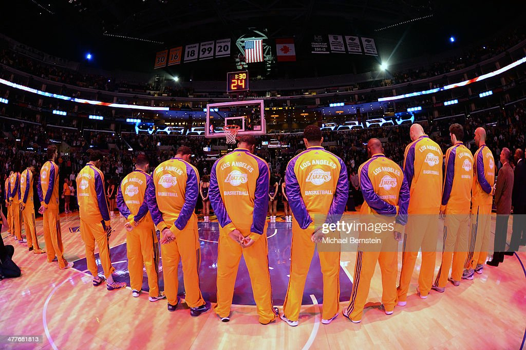 Members of the Los Angeles Lakers stand in observance of the national anthem before a game against the New Orleans Pelicans at Staples Center on November 12, 2013 in Los Angeles, California.