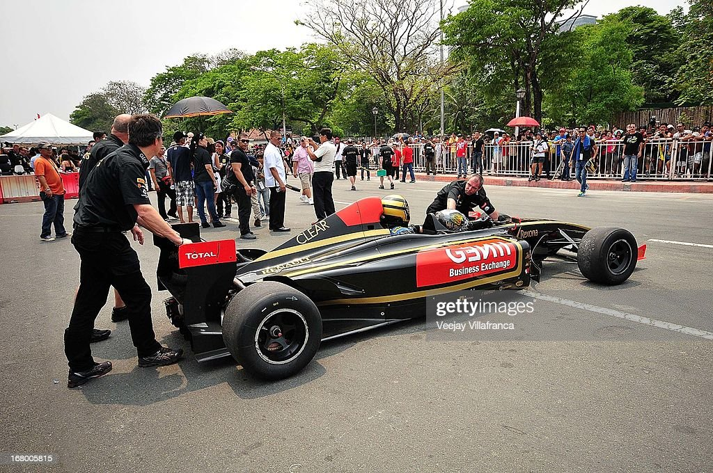 Members of the Lotus Formula 1 team assist the reserve driver carrying a VIP in the F1 car on May 4, 2013 in Manila, Philippines. The Formula 1 Lotus team was in the Philippines for a promotional tour and also hoping to gather support for their Filipino-Swiss junior driver and also to drum up interest in the sport.