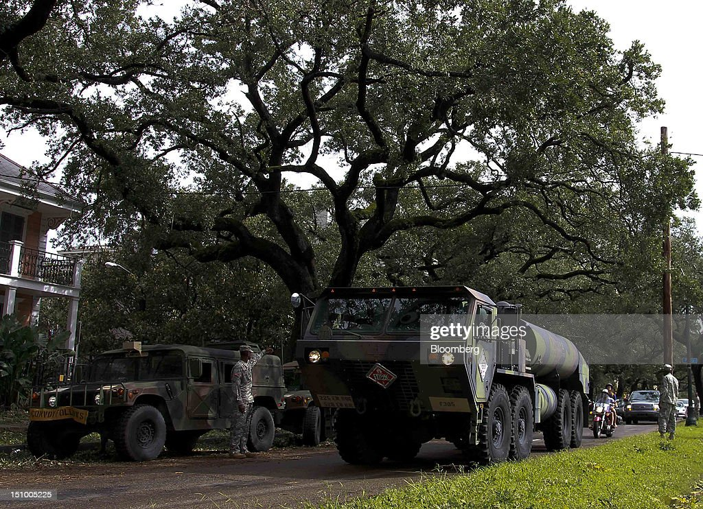 Members of the Louisiana National Guard assist in the clean-up of trees and debris left by Hurricane Isaac in New Orleans, Louisiana, U.S., on Thursday, Aug. 30, 2012. Heavy rain and flooding spread inland from Tropical Storm Isaac as rising water forced evacuations in coastal areas of southeast Louisiana. Photographer: Derick E. Hingle/Bloomberg via Getty Images