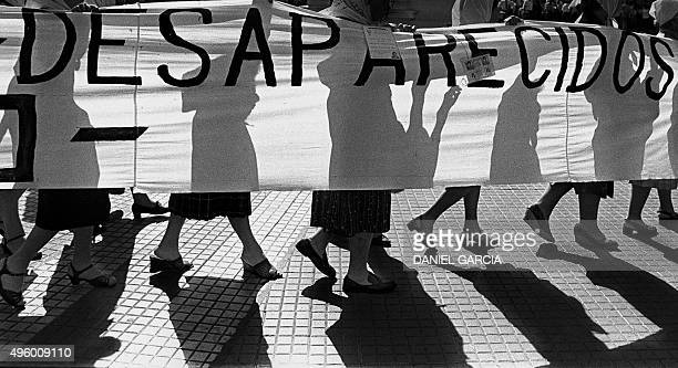 Members of the 'Madres de Plaza de Mayo' human rights organization hold a banner claiming for their missing sons and daughters as they walk in front...