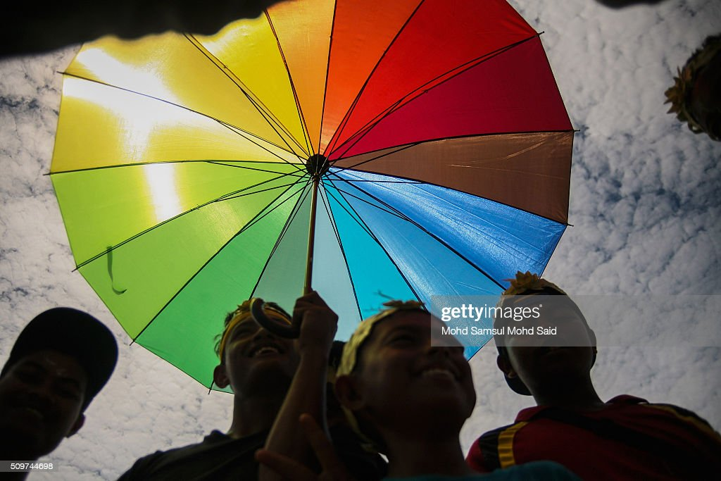 Members of the Mah Meri tribe watch a performance under a rainbow coloured umbrella of the 'Main Jo-oh' dance, part of the Puja Pantai' rituals a thanksgiving ritual to appease the spirits of the seas at Pulau Carey, Straits of Malacca beach on February 12, 2016 in Pulau Carey, Malaysia. Every year, the indigenous people of Mah Meri village, located in Pulau Carey, about 140 km (87 miles) southwest of Kuala Lumpur, perform the 'Puja Pantai' ritual prayer and 'Main Jo-oh' dance to appease the spirits of the seas and celebrate the New Year.