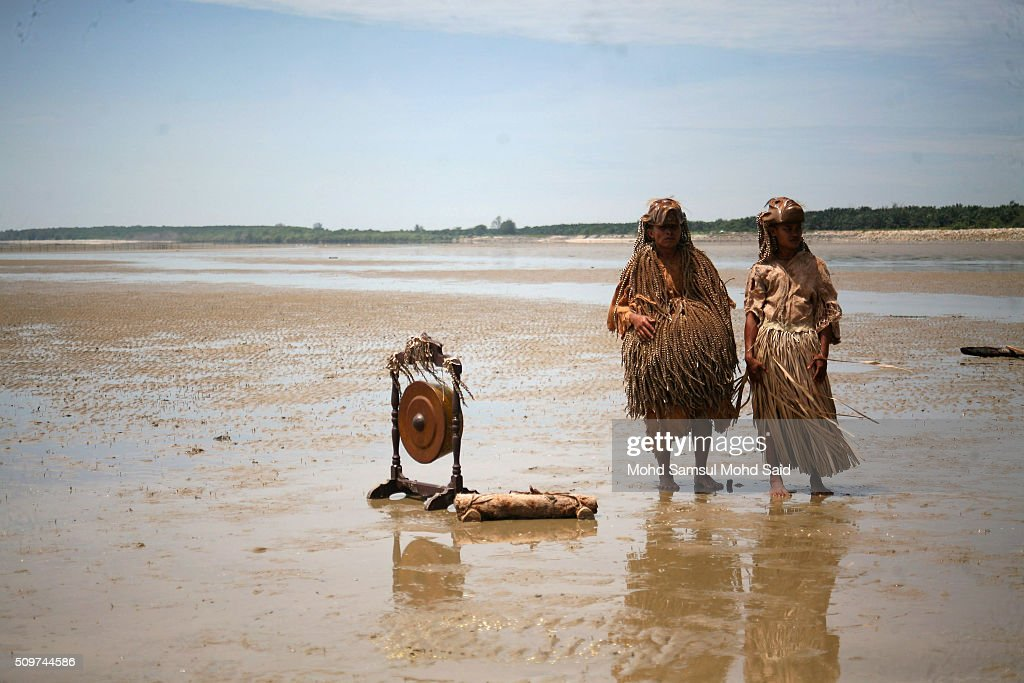 Members of the Mah Meri tribe wearing a traditional costume stand at the beach after their 'Puja Pantai', a thanksgiving ritual to appease the spirits of the seas on February 12, 2016 in Pulau Carey, Malaysia. Every year, the indigenous people of Mah Meri village, located in Pulau Carey, about 140 km (87 miles) southwest of Kuala Lumpur, perform the 'Puja Pantai' ritual prayer and 'Main Jo-oh' dance to appease the spirits of the seas and celebrate the New Year.