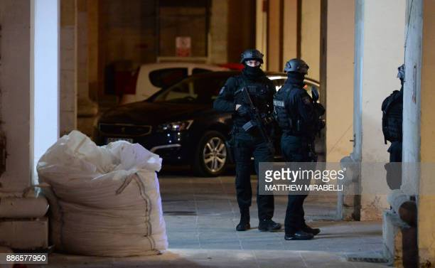 Members of the Malta Police Force guard the back door of the law courts in Valletta Malta on December 6 after three men were charged with the murder...