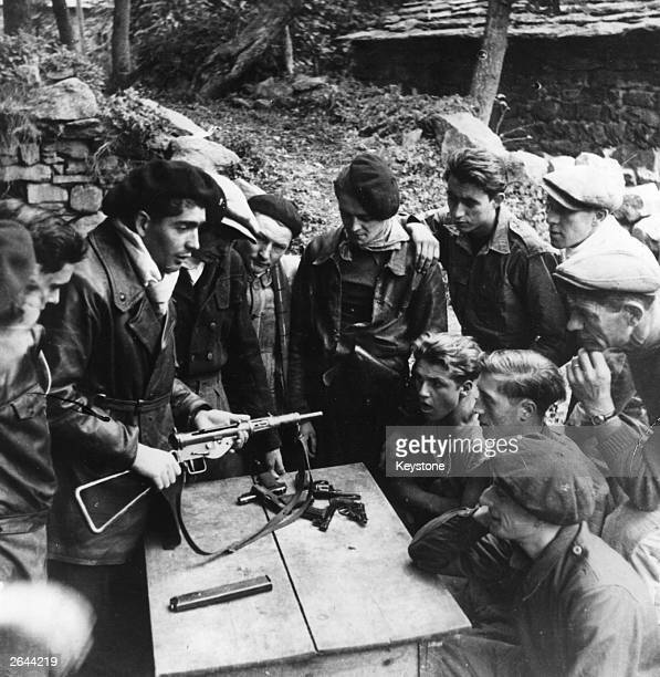 Members of the Maquis the French Resistance study the mechanism and maintenance of weapons dropped by parachute in the Haute Loire They include a...