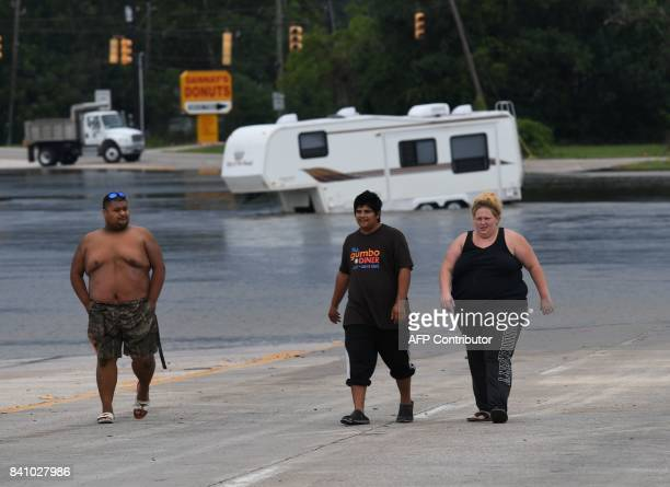 Members of the Martinez family turn back after trying to retrieve their car which they abandoned during the height of Hurricane Harvey in Houston...