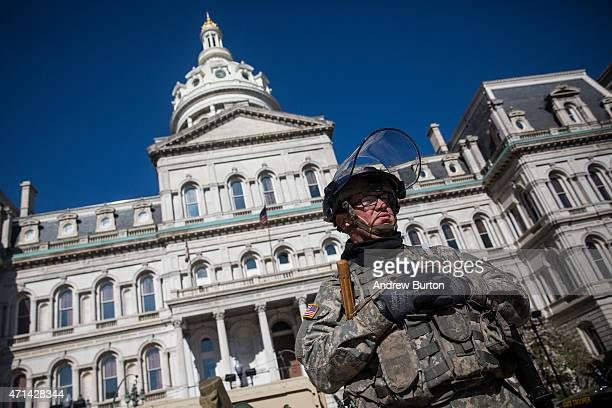 Members of the Maryland National Guard stand guard over the Baltimore city hall building after riots broke out yesterday after the funeral of Freddie...