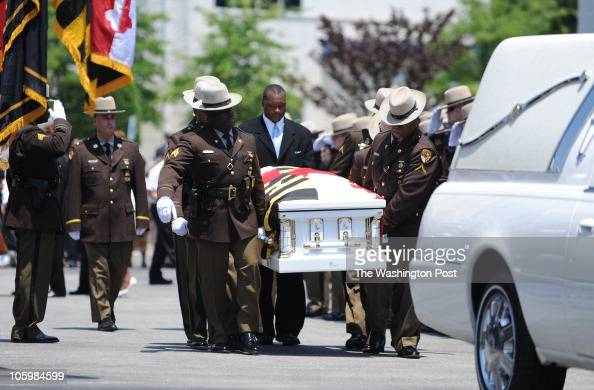 Members of the Maryland State Police carry the body of Wesley W Brown to the hearse in preparation for heading to the cemetery following the funeral...