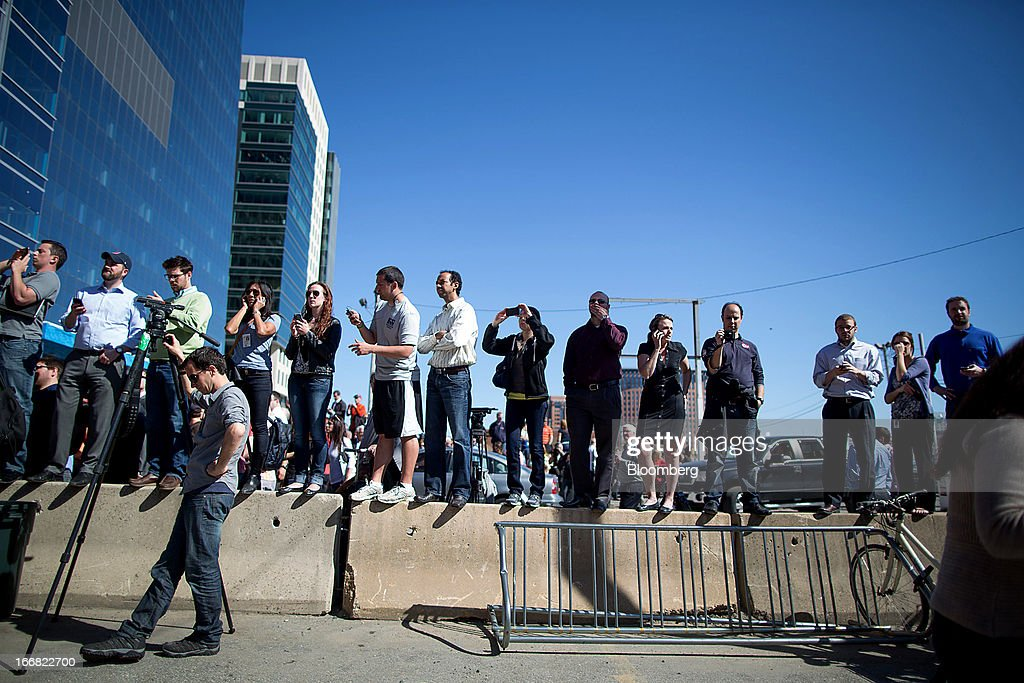 Members of the media and onlookers stand on a concrete barricade outside of the John Joseph Moakley United States Courthouse in Boston, Massachusetts, U.S., on Wednesday, April 17, 2013. Investigators have video of a possible suspect in the Boston Marathon bombings though no one is under arrest in the case, according to federal law enforcement officials. Photographer: Scott Eisen/Bloomberg via Getty Images