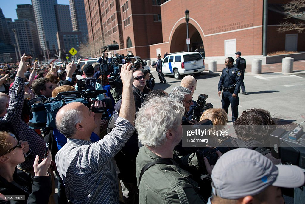 Members of the media and onlookers stand outside of the John Joseph Moakley United States Courthouse in Boston, Massachusetts, U.S., on Wednesday, April 17, 2013. Investigators have video of a possible suspect in the Boston Marathon bombings though no one is under arrest in the case, according to federal law enforcement officials. Photographer: Scott Eisen/Bloomberg via Getty Images