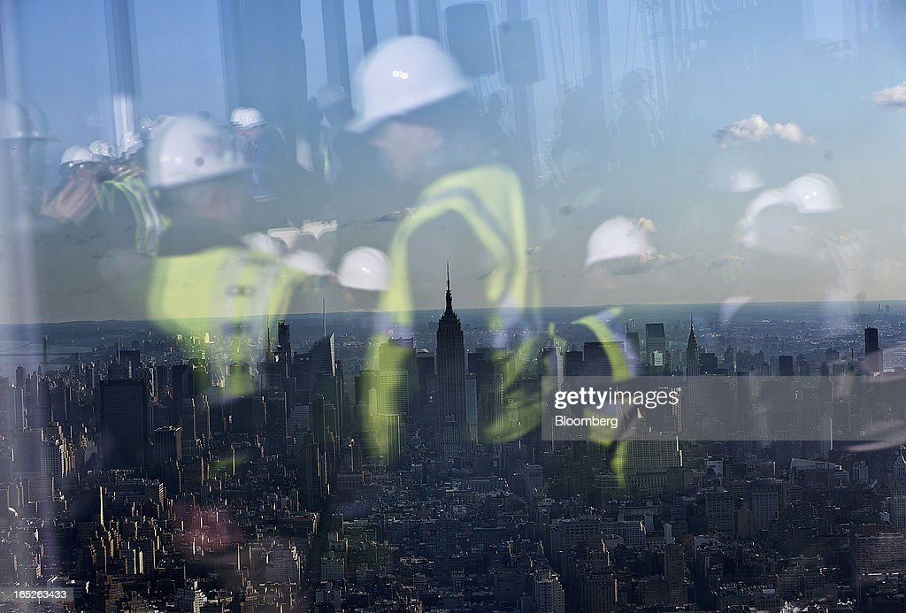 Members of the media are reflected in the window of the One World Trade Center observation deck as the Manhattan skyline stands in New York, U.S., on Tuesday, April 2, 2013. The observation deck at One World Trade Center, expected to open in 2015, will occupy the tower's 100th through 102nd floors. Guests visiting the observation deck will see a 'pre-show' about the creation of the building while waiting in line in the lobby. Photographer: Victor J. Blue/Bloomberg via Getty Images