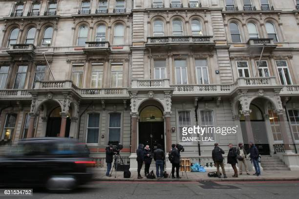 Members of the media are seen outside the main entrance to the building housing the offices of business consultants Orbis Business Intelligence Ltd...