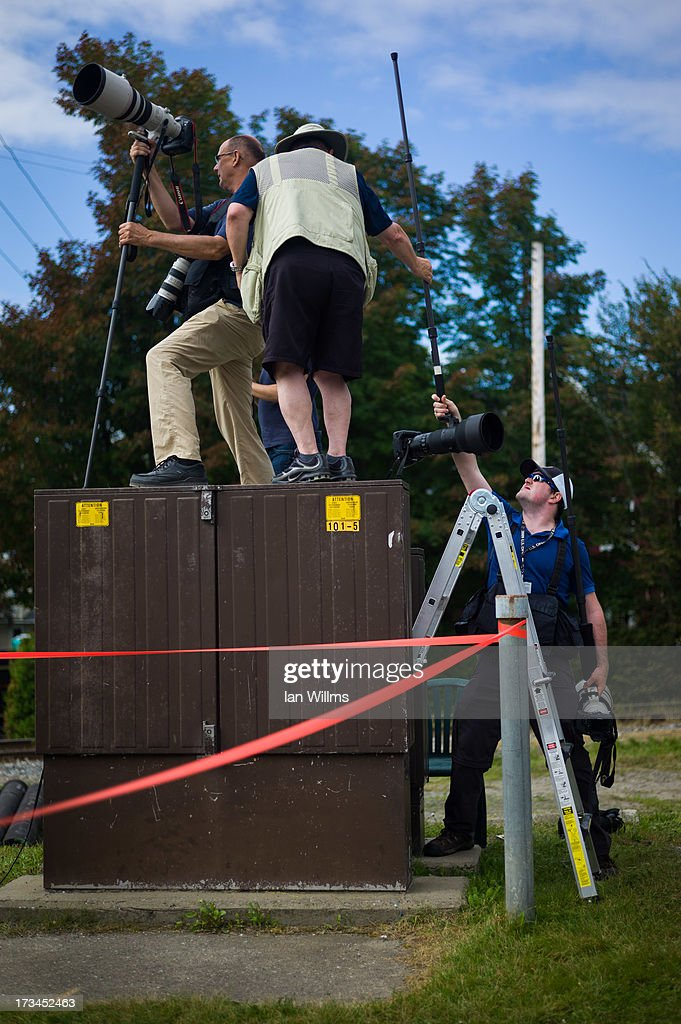 Members of the media attempt to make photographs of the 'red zone' crash site, on July 14, 2013 in Lac-Megantic, Quebec, Canada. A train derailed and exploded into a massive fire that flattened dozens of buildings in the town's historic district, leaving 60 people dead or missing in the early morning hours of July 6.