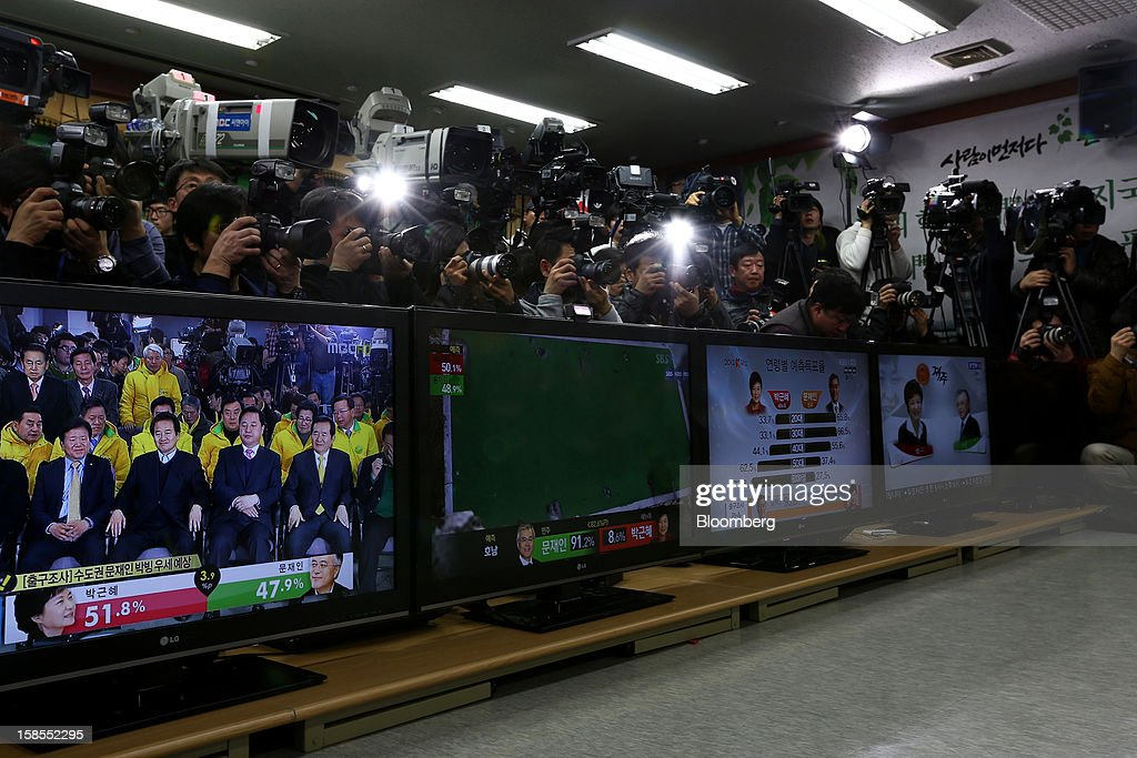 Members of the media crowd behind television screens showing exit poll results for the presidential election at the headquarters of the main opposition Democratic United Party in Seoul, South Korea, on Wednesday, Dec. 19, 2012. South Korean ruling party presidential candidate Park Geun Hye leads opposition nominee Moon Jae In in a close race to lead Asia's fourth-biggest economy, exit polls showed. Photographer: SeongJoon Cho/Bloomberg via Getty Images