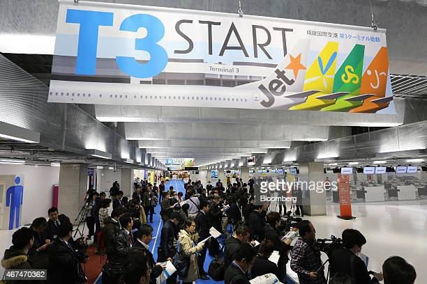 Members of the media crowd under a sign announcing the start of Terminal 3 at Narita Airport in Narita Japan on Wednesday March 25 2015The airport...