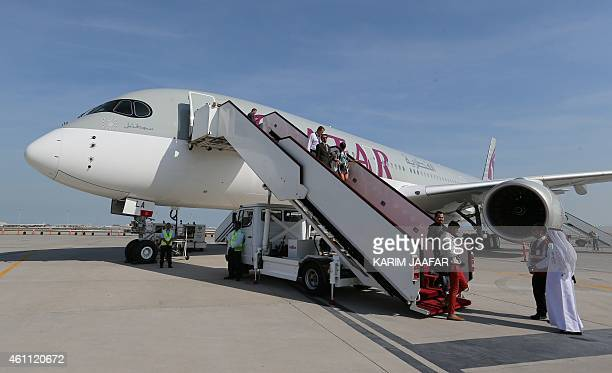 Members of the media disembark from a Qatar Airways Airbus A350XWB at the Doha Airport in Doha on January 72015 Qatar Airways presented the new...