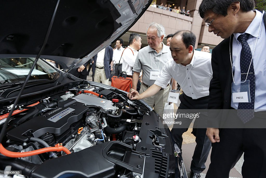 Members of the media examine a Honda Motor Co. Accord hybrid sedan displayed at its unveiling in Tokyo, Japan, on Thursday, June 20, 2013. Honda, Japan's third-largest carmaker, unveiled a hybrid sedan at a 20 percent higher price than Toyota Motor Corp.'s gasoline-electric Camry, betting drivers will pay extra for fuel economy. Photographer: Kiyoshi Ota/Bloomberg via Getty Images