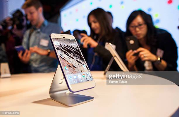 Members of the media examine Google's Pixel phone during an event to introduce Google hardware products on October 4 2016 in San Francisco California...