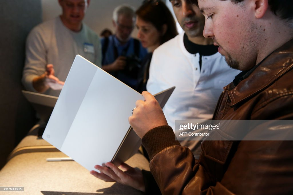 Members of the media examine the new Pixelbook laptop at a product launch event on October 4, 2017 at the SFJAZZ Center in San Francisco, California. / AFP PHOTO / Elijah Nouvelage