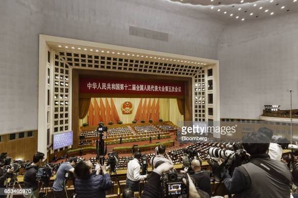 Members of the media film and photograph delegates inside the Great Hall of the People during the closing ceremony of the National People's Congress...
