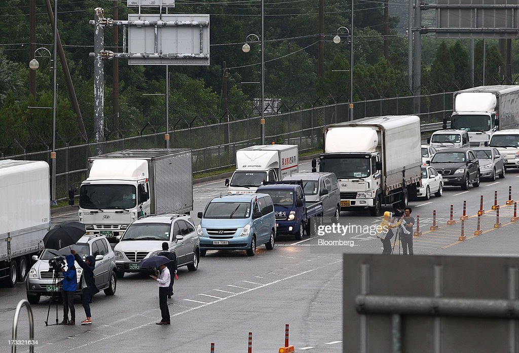 Members of the media film vehicles at the Customs, Immigration and Quarantine (CIQ) office as they travel toward the Gaeseong Industrial Complex, on a road linked to North Korea, near the demilitarized zone (DMZ) in Paju, South Korea, on Friday, July 12, 2013. North Korea notified South Korea today that it has deferred two separate sets of talks on the tours and the family reunions it proposed yesterday, and said it wants to focus on the ongoing dialog to reopen the joint Gaeseong industrial zone, the Souths Unification Ministry said in an e-mailed statement. The two sides yesterday decided to hold talks in Gaeseong on July 15, which will be their third round in one week, on normalizing operations in Gaeseong after the North unilaterally recalled its workers in April. Photographer: SeongJoon Cho/Bloomberg via Getty Images