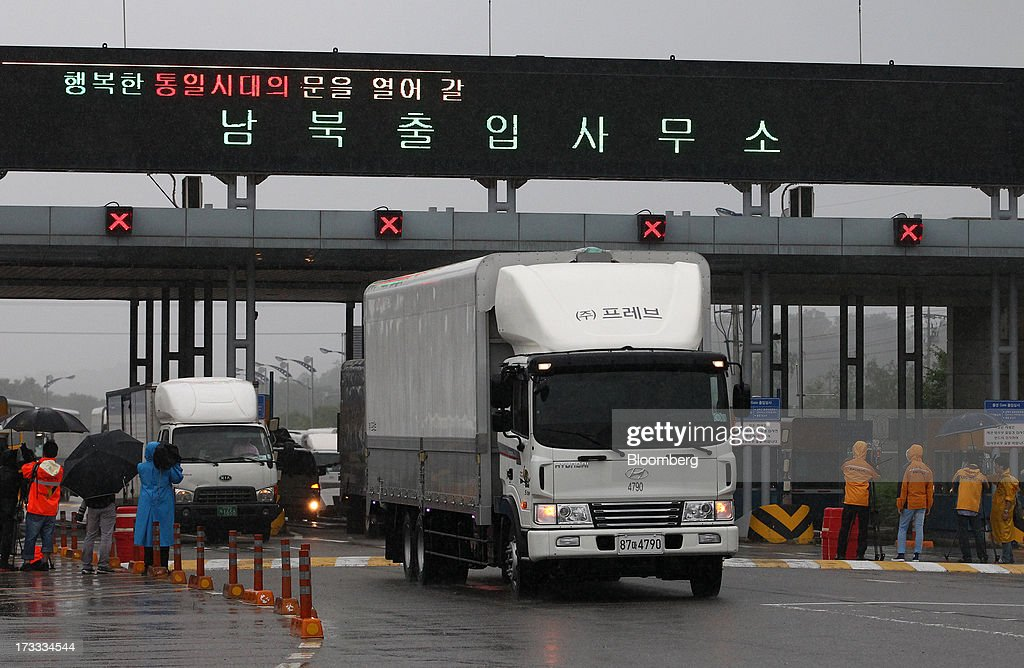Members of the media film vehicles returning from the Gaeseong Industrial Complex as they pass a gate at the Customs, Immigration and Quarantine (CIQ) office near the demilitarized zone (DMZ) in Paju, South Korea, on Friday, July 12, 2013. North Korea notified South Korea today that it has deferred two separate sets of talks on the tours and the family reunions it proposed yesterday, and said it wants to focus on the ongoing dialog to reopen the joint Gaeseong industrial zone, the Souths Unification Ministry said in an e-mailed statement. The two sides yesterday decided to hold talks in Gaeseong on July 15, which will be their third round in one week, on normalizing operations in Gaeseong after the North unilaterally recalled its workers in April. Photographer: SeongJoon Cho/Bloomberg via Getty Images
