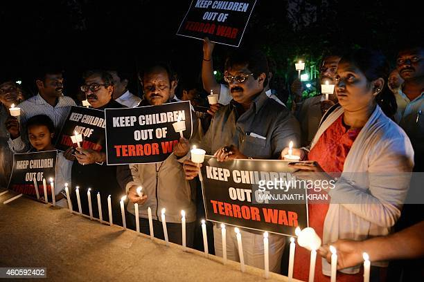Members of the media fraternity and political activists hold placards and candles as they pay tribute to Pakistan children and staff killed in a...