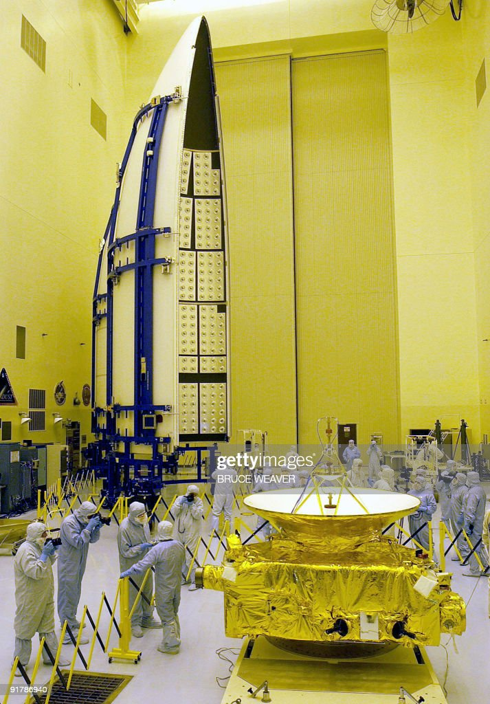 Members of the media garbed in protective uniforms view NASA's New Horizons spacecraft before the launch faring 04 November 2005 in the Payload...