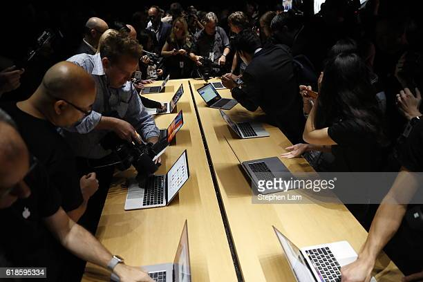 Members of the media gather around a table displaying the new Apple MacBook Pro laptop after the product launch event on October 27 2016 in Cupertino...