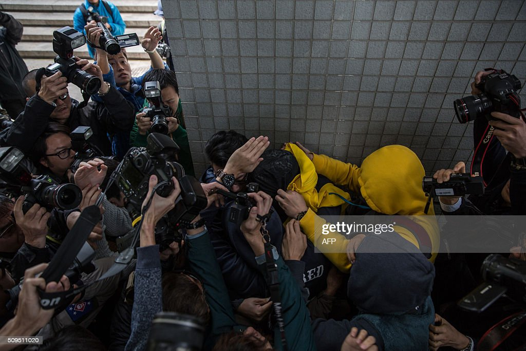 Members of the media gather as a supporter (top R-yellow jacket) helps escort a protester (top C-covered with a black and yellow jacket), who is facing one count of taking part in a riot on February 9 in the district of Mongkok, to a taxi after a court hearing in Hong Kong on February 11, 2016. More than 30 people were expected to appear in court charged with rioting after clashes erupted in the city over official attempts to remove illegal street hawkers during the Lunar New Year. AFP PHOTO / DALE DE LA REY / AFP / DALE de la REY