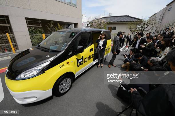 Members of the media gather near an electric car for the Robonekoyamato autonomous van delivery service operated by Yamato Transport Co and DeNA Co...
