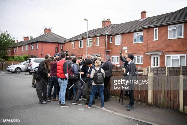 Members of the media huddle to interview a neighbour as forensic teams search the former home of terrorist Salman Abedi on May 24 2017 in Manchester...