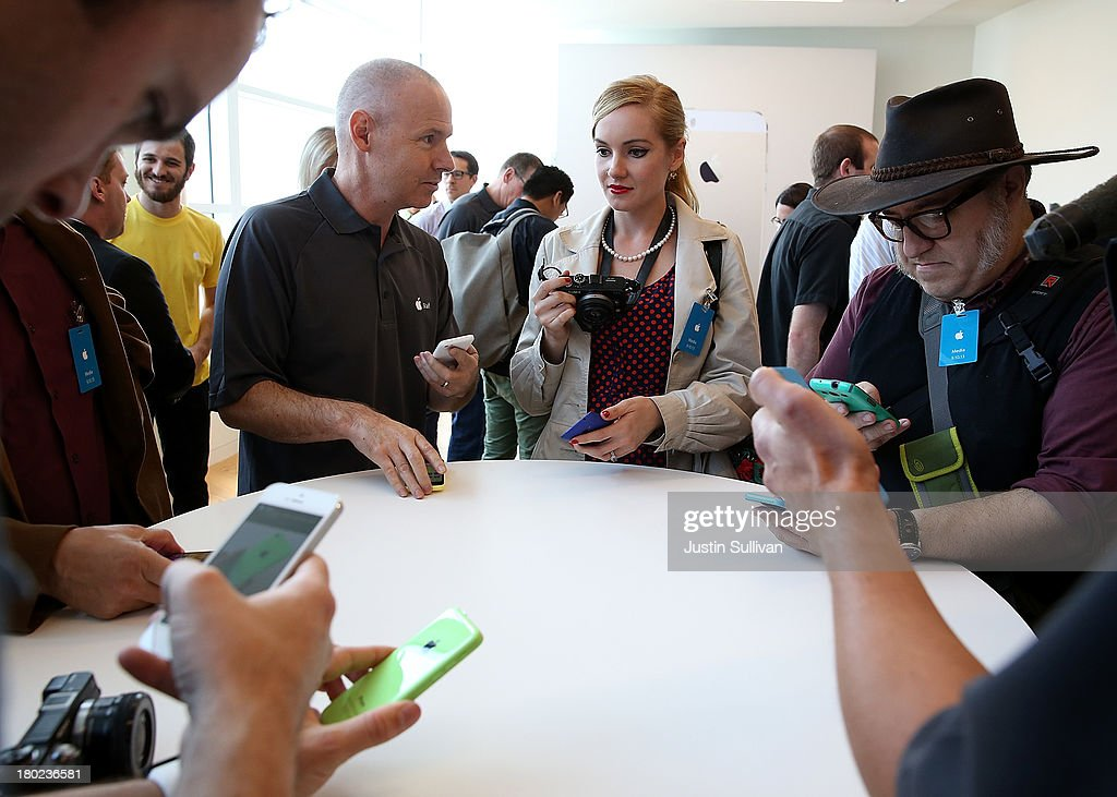 Members of the media inspect the new iPhone 5C during an Apple product announcement at the Apple campus on September 10, 2013 in Cupertino, California. The company launched the new iPhone 5C model that will run iOS 7 is made from hard-coated polycarbonate and comes in various colors and the iPhone 5S that features fingerprint recognition security.