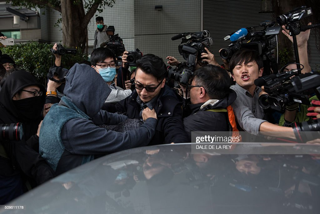 Members of the media jostle for position to cover as supporters (2nd and 3rd L) help escort a protester (lower L-covered with a grey jacket), who is facing one count of taking part in a riot on February 9 in the district of Mongkok, into a taxi after a court hearing in Hong Kong on February 11, 2016. More than 30 people were expected to appear in court charged with rioting after clashes erupted in the city over official attempts to remove illegal street hawkers during the Lunar New Year. AFP PHOTO / DALE DE LA REY / AFP / DALE de la REY