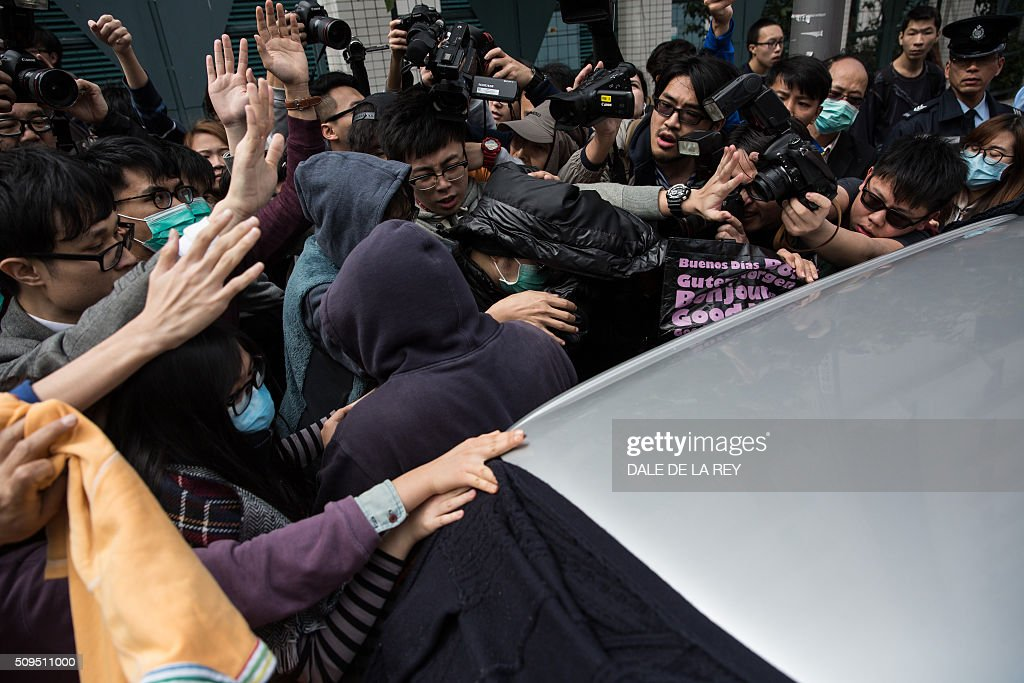 Members of the media jostle for position to cover as supporters of a protester (C-covered with a black jacket), who is facing one count of taking part in a February 9 riot in the district of Mongkok, help him into a taxi after a court hearing in Hong Kong on February 11, 2016. More than 30 people were expected to appear in court charged with rioting after clashes erupted in the city over official attempts to remove illegal street hawkers during the Lunar New Year. AFP PHOTO / DALE DE LA REY / AFP / DALE de la REY