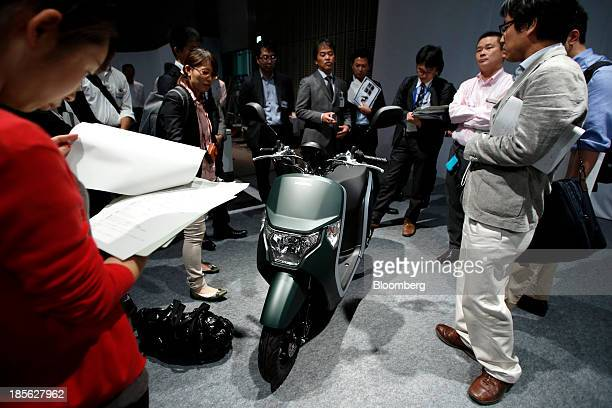 Members of the media look at a Honda Motor Co Dunk scooter displayed at a media event in Tokyo Japan on Wednesday Oct 16 2013 Honda will premier the...
