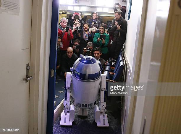 Members of the media look at Star Wars character R2D2 as it visits the Brady Briefing Room at the White House December 18 2015 in Washington DC The...