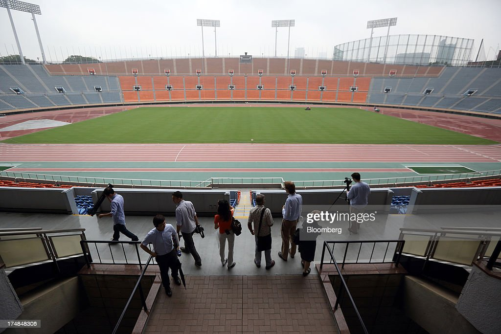 Members of the media look at the existing National Olympic Stadium built for the 1964 Olympic games, which will be demolished to make way for a new venue designed by architect Zaha Hadid, during a media tour for Japan's bid for the 2020 Olympic and Paralympic Games in Tokyo, Japan, on Monday, July 29, 2013. Tokyo, the front-runner city to host the 2020 Olympics, is planning its biggest housing complex in 42 years to lodge athletes, a move that could benefit developers such as Shimizu Corp. and Mitsubishi Estate Co. Photographer: Tomohiro Ohsumi/Bloomberg via Getty Images