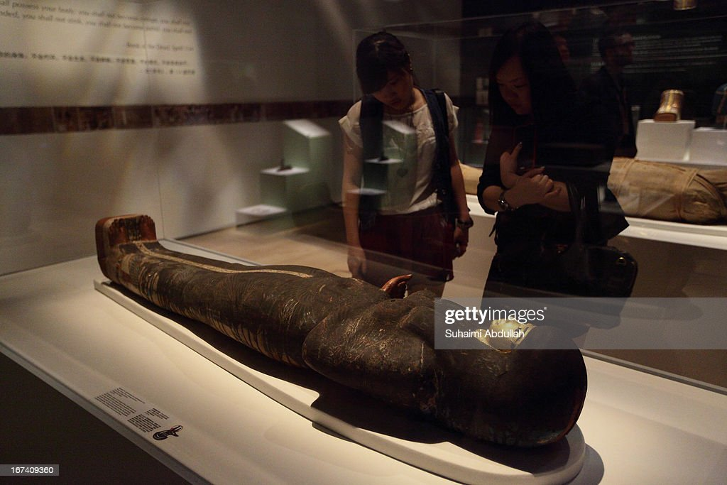 Members of the media look at the Mummy of Tjayasetimu in cartonnage case exhibit during a media preview of the Mummy: Secrets of the Tomb exhibition at ArtScience Museum on April 25, 2013 in Singapore. The exhibition includes more than 100 artifacts and six mummies from the heralded ancient Egyptian collection of the British Museum. Among the mummies displayed is the Egyptian temple priest, Nesperennub who lived 3,000 years ago. The exhibition will run from April 27 till November 4, 2013.
