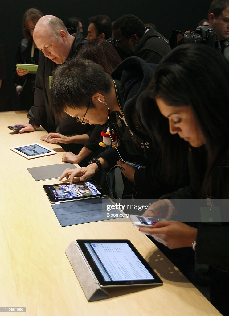 Members of the media look at the new version Apple Inc.'s iPad during an Apple event in San Francisco, California, U.S., on Wednesday, March 7, 2012. Apple Inc. introduced a new version of the iPad, beefing up its two-year-old mobile computer with a sharper screen to widen its lead over Amazon.com Inc., Microsoft Corp. and Google Inc. in the tablet market. Photographer: Tony Avelar/Bloomberg via Getty Images