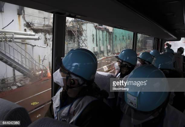Members of the media look at the Unit 4 reactor building at Tokyo Electric Power Co's Fukushima Daiichi nuclear power plant in Okuma Fukushima Japan...