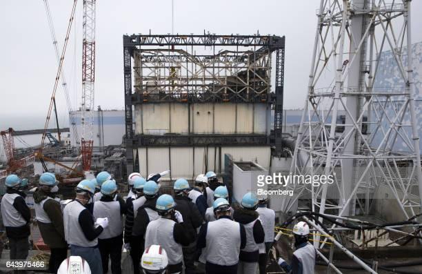 Members of the media look out at the Unit 1 reactor building at Tokyo Electric Power Co's Fukushima Daiichi nuclear power plant in Okuma Fukushima...