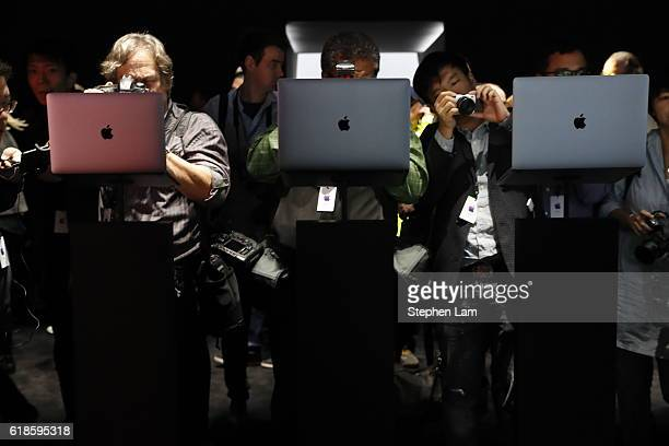 Members of the media photograph the new Apple MacBook Pro laptop during a product launch event on October 27 2016 in Cupertino California Apple Inc...