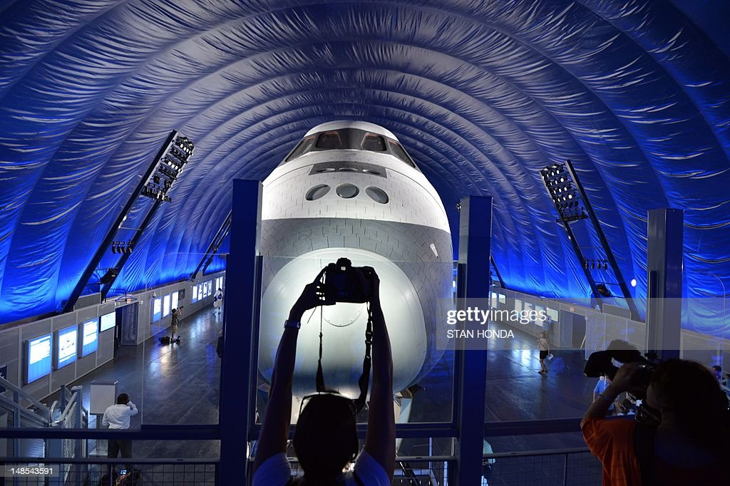 Members of the media photograph the Space Shuttle Enterprise on display at the Intrepid Sea, Air & Space Museum's Space Shuttle Pavilion during a press preview July 18, 2012 in New York. The exhibit will officially open to the public July 19. AFP PHOTO/Stan HONDA