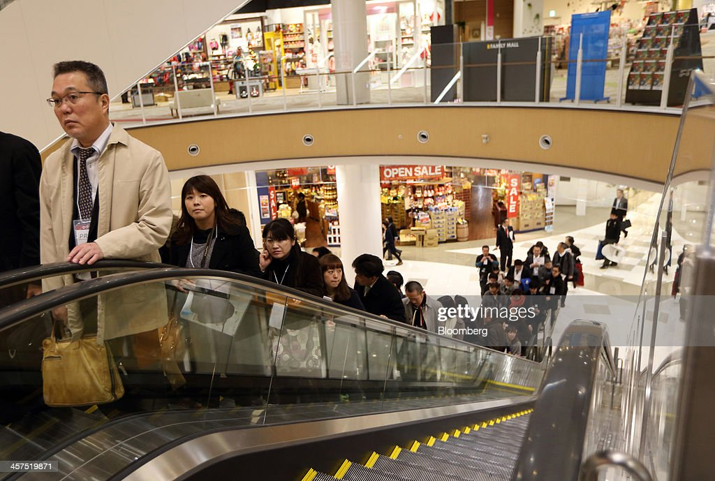 Members of the media ride an escalator in Aeon Mall Makuhari Shintoshin shopping mall, operated by Aeon Mall Co., during a media preview ahead of the mall's opening in Chiba, Japan, on Monday, Dec. 16, 2013. Large Japanese businesses pared their projections for capital spending this fiscal year, signaling challenges for Abenomics as a sales-tax increase looms in April. Photographer: Tomohiro Ohsumi/Bloomberg via Getty Images