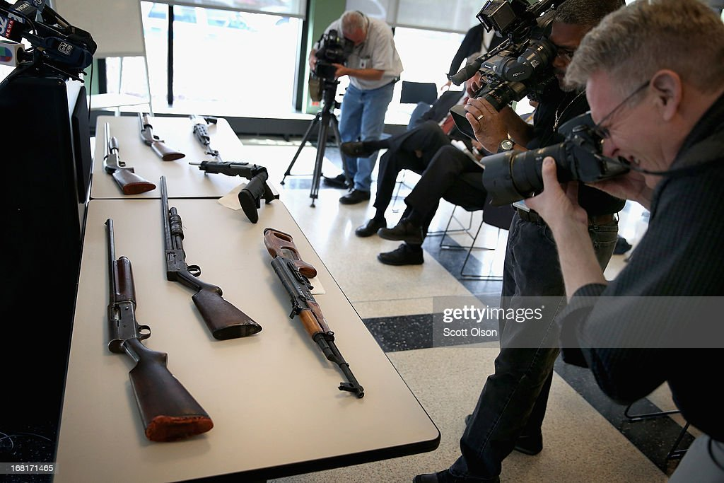 Members of the media shoot a small display of guns prior to a press conference with Chicago Police Superintendent Garry McCarthy in the Englewood neighborhood on May 6, 2013 in Chicago, Illinois. McCarthy said Chicago police confiscate an average of more than 130 illegal guns each week. On Saturday about a mile from the police station where McCarthy spoke, 47-year-old Denise Warfield was found stabbed to death inside as abandoned church building. Less than two blocks from Warfield's murder, three men were shot while walking near the First Mennonite Church of Chicago shortly after midnight Monday morning.