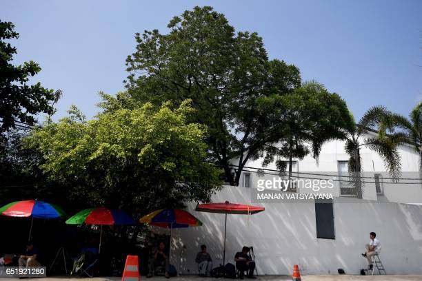 Members of the media sit in the shade outside the North Korean embassy in Kuala Lumpur on March 11 2017 Malaysia's police chief confirmed March 10...