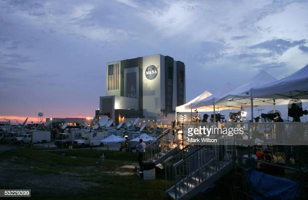 Members of the media stand camped out near the Vehicle Assembly Building as the sun sets at the Kennedy Space Center July 12 2005 in Cape Canaveral...