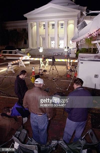 Members of the media stand in front of the Florida State Supreme Court building in downtown Tallahassee 12 December 2000 as they watch a TV monitor...